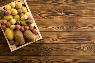 Small wooden crate filled with fresh potatoes