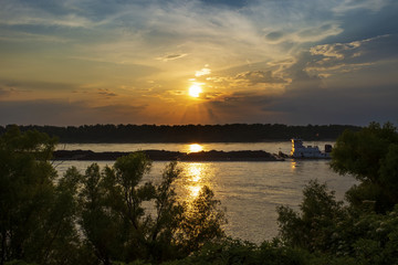 A towboat with barges in the Mississippi river at sunset near the city of Vicksburg in the State of Mississippi, USA.