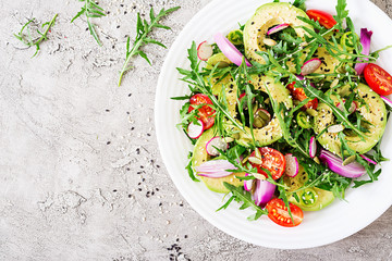 Diet menu. Healthy salad of fresh vegetables - tomatoes, avocado, arugula, radish and seeds on a bowl. Vegan food. Flat lay. Top view