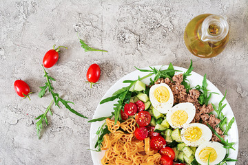 Pasta salad with fresh vegetables, eggs and tuna in a white bowl. Lunch food. Top view.  Flat lay