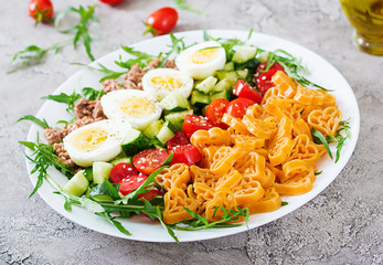 Pasta salad with fresh vegetables, eggs and tuna in a white bowl. Lunch food.
