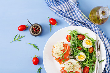Printed kitchen splashbacks Ready meals Tasty breakfast. Open sandwiches with salmon, cream cheese and rye bread in a white plate and salad with tomato, egg and arugula. Top view. Flat lay