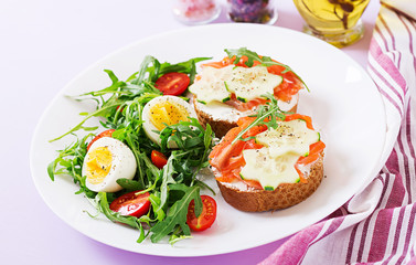 Tasty breakfast. Open sandwiches with salmon, cream cheese and rye bread in a white plate and salad with tomato, egg and arugula.