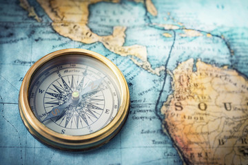 Spoed Foto op Canvas Wereldkaart Magnetic compass on world map.Travel, geography, navigation, tourism and exploration concept background. Macro photo. Very shallow focus.