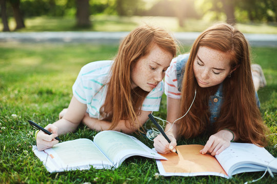 I am tired, write homework instead of me. Portrait of bored younger sister with ginger hair and freckles leaning on sibling shoulder while lying together on grass and writing essays, helping to study