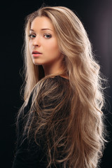 View over shoulder of beautiful and sexy blonde girl posing in studio on grey background and looking at camera. Beautiful and serious model wearing black with shiny long hair, perfect makeup.