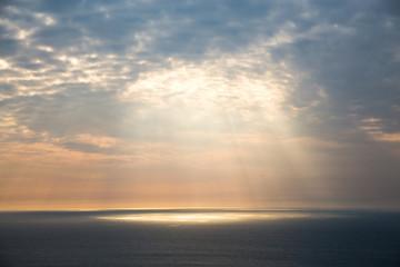 Golden light breaks through the grey sky. The sun's rays look through the clouds over the ocean.