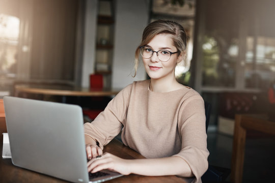 Creative and attractive female graphic designer working under project while sitting in cafe with laptop, gazing at camera with slight tired smile, arranging meeting via notebook with clients