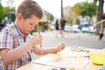 Cute little boy drawing with colorful paints in fall park. Creative child painting on nature. Outdoors activity for toddler kid.