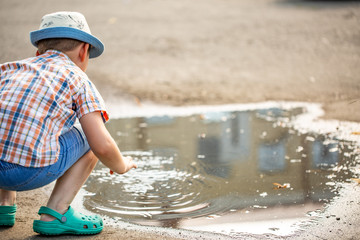 Children's outdoor play. sitting on his haunches near the large puddles.