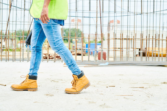 Low section portrait of unrecognizable worker wearing jeans and boots crossing construction site, copy space
