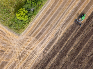 Wall Mural - An agricultural field after harvesting with tractor plowing the soil on a summer day. Top view