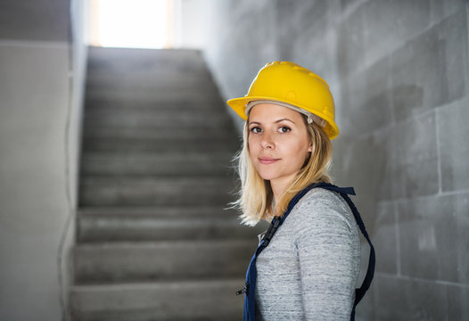 Young woman worker with a yellow helmet on the construction site.