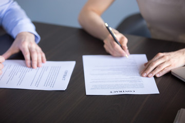 Close up of business partners sign cooperation contract during office corporate meeting, hired employee and ceo put signature on agreement after successful interview. Collaboration, employment concept