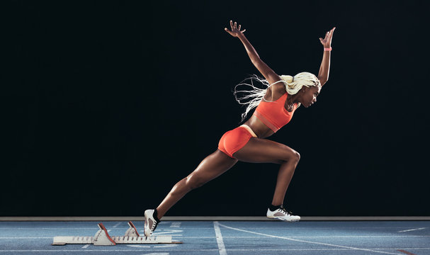 Woman athlete taking off from starting block on a running track