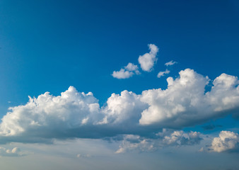 White fluffy clouds in the blue sky at sunset in the summer day.