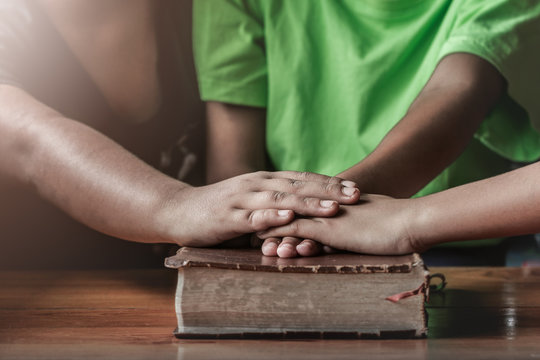 christian children small group put hands together on the Bible, prayer meeting concept