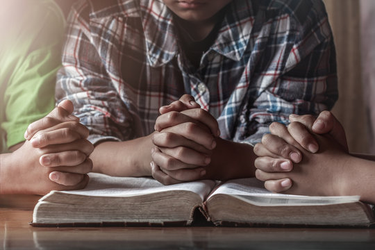 christian children group praying on wooden table with open bible, prayer meeting concept