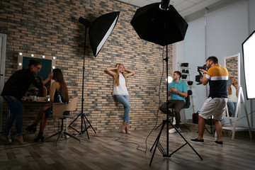 Professional team working with model in photo studio