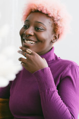 Smiling black woman with pink hair