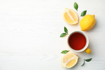 Cup of black tea and lemons on wooden table, top view