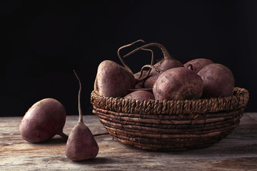 Basket with whole fresh beets on wooden table