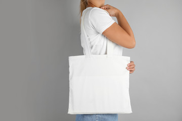Woman with tote bag on grey background. Mock up for design