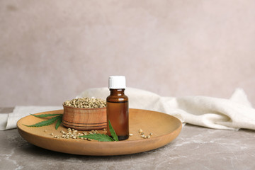 Plate with hemp seeds and bottle of extract on table