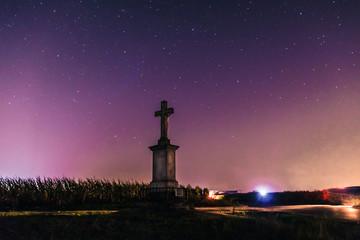 murowany krzyż wśród pól na tle gwieździstego nieba