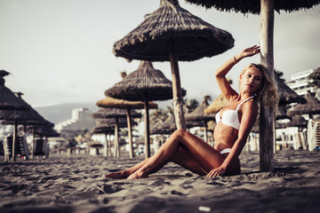 sensual portrait of beautiful yhoung blonde female taking bathsun at the beach sit down on the sand with white bikini on the dark skin. attractive girl on vacation enjoying the sun outdoor