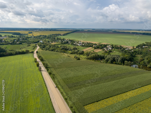 Wall mural Aerial view from a bird's-eye view to a rural landscape with a village, dirt road and agricultural fields of planted crops.