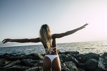 wanderlust and traveler blonde female young people opening arms and enjoying the sunset over the ocean. happiness and freedom concept for tanner babe with white slim bikini.