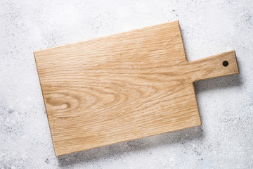 Empty wooden cutting board on white stone table.