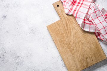 Empty wooden cutting board and tablecloth on white stone table.