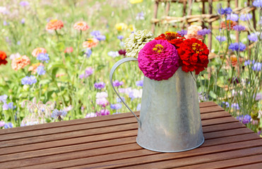 Zinnias in a rustic pitcher on a garden table