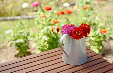 Rustic pitcher holding zinnia flowers on a garden table