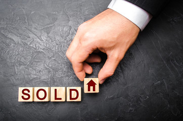 realtor's hand puts a cube with a picture of the house to the word sold. Concept of selling a house, apartment, real estate. market of immobility. Trade of property. Affordable housing. Hand in suit.