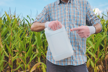 Farmer holding pesticide chemical jug in cornfield