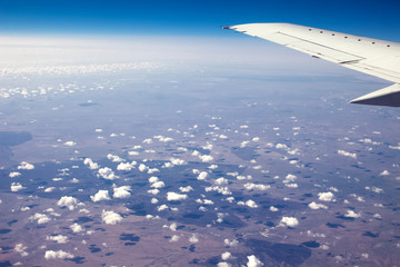 Airplain window seat view of big white thick fluffy clouds with a clear blue sky at the background