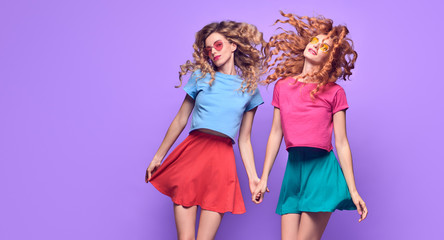 Wall Mural - Full-length portrait Two Girl with Wavy Hairstyle Having Fun Dance. Young Beautiful Pretty Model Woman in Fashion Stylish Summer Outfit. Crazy Sisters Friends laughing on Purple