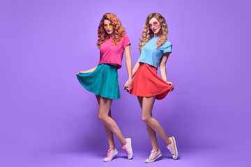 Wall Mural - Two Playful Sisters Having Fun in Studio on Purple. Young Beautiful Hipster Girl in Stylish Sunglasses, Fashion Trendy Outfit. Blond Redhead Woman Smiling, Happy positive emotion