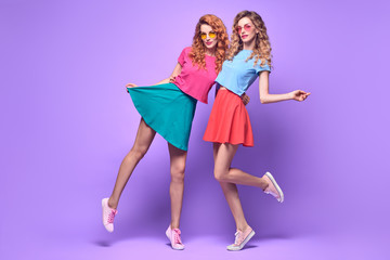 Wall Mural - Two Girs Fooling Around in Studio. Young Beautiful Playful Sisters Twins Having Fun Dance, Trendy Curly Hairstyle, Fashion Stylish Outfit. Cheerful Blond Redhead Woman on Purple