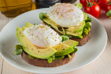 Avocado toast, cherry tomato and poached eggs on wooden background. Breakfast with vegetarian food, healthy diet concept.