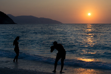 Silhouette man is taking pictures of a silhouette girl who is playing with waves at Myrtos beach in Kefalonia Greece. Sunset background