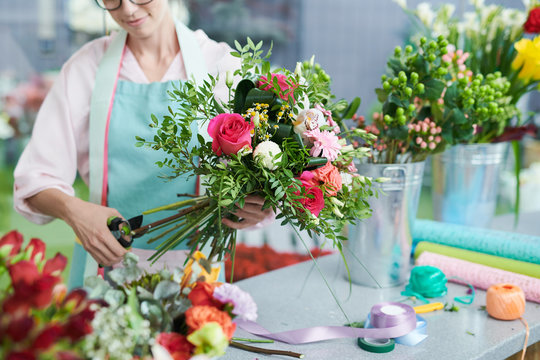Crop view of smiling woman arranging flower bouquet in shop