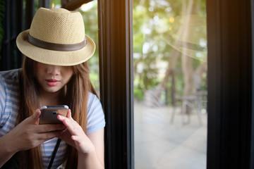 Woman used smartphone in coffee shop beside windows