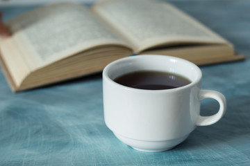 A book and a cup of hot drink, coffee.