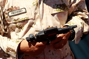 A soldier holds a toy gun during an exchange of toy weapons for toys as part of the campaign 'Playing without violence' organised by the Mexican Army in Ciudad Juarez