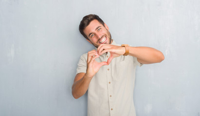 Handsome young man over grey grunge wall wearing summer shirt smiling in love showing heart symbol and shape with hands. Romantic concept.