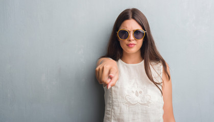 Young brunette woman over grunge grey wall wearing retro sunglasses pointing with finger to the camera and to you, hand sign, positive and confident gesture from the front